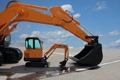 Duas máquinas escavadoras em uma plataforma concreta Fotos de Stock