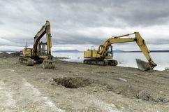 Duas máquinas escavadoras que trabalham em uma construção de estradas nova Foto de Stock Royalty Free