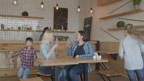 Duas mães adultas com as crianças que encontram-se no café filme