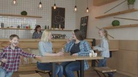 Duas mães solteiras com as crianças preteen que encontram-se no café filme