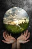 Duas mãos abertas levantam e a paisagem do mundo da bola com campo e por do sol verdes Fotografia de Stock Royalty Free