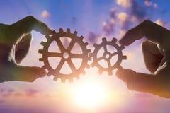 Duas mãos conectam as engrenagens, os detalhes do enigma contra o céu com por do sol foto de stock