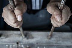 Duas mãos da cadeia que guardam barras da prisão fotografia de stock royalty free