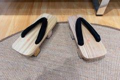 Duas mãos da madeira, do adulto e das crianças Decoração das escovas no banheiro Tamanco japonês de madeira das sandálias imagens de stock royalty free