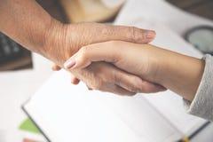 Duas mãos da mulher na tabela de funcionamento imagens de stock