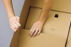 Duas mãos da mulher que abrem a caixa de cartão grande Imagem de Stock Royalty Free