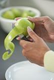 Duas mãos de uma mulher que usa a faca para descascar uma pele da maçã Fotos de Stock