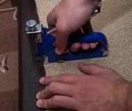 Duas mãos do homem que usam o paricle de estofamento do grampeador embarcam com couro sintético foto de stock