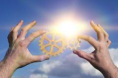 Duas mãos dos homens de negócios conectam as engrenagens, partes de um enigma O conceito de uma ideia do negócio Imagens de Stock