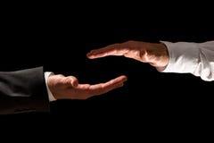 Duas mãos dos homens de negócios dos quadros da parte superior e da parte inferior Foto de Stock
