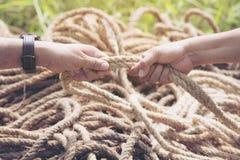 Duas mãos dos povos que puxam a corda Imagens de Stock Royalty Free