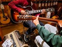 Duas mãos humanas que jogam a guitarra acústica em uma loja da guitarra fotografia de stock