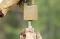 Duas mãos nas luvas com chave e o cadeado destravado Fotos de Stock