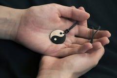 Duas mãos que guardam a colar de yang do yin da pérola no fundo escuro imagem de stock royalty free