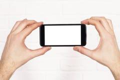 Duas mãos que guardam o telefone Fotografia de Stock