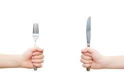 Duas mãos que prendem a forquilha e a faca Imagens de Stock Royalty Free
