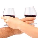 Duas mãos que prendem vidros de vinho vermelho Fotografia de Stock Royalty Free