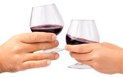 Duas mãos que prendem vidros de vinho vermelho Imagem de Stock Royalty Free