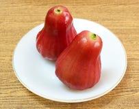 Duas maçãs da água vermelha na placa branca imagem de stock