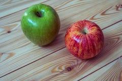 Duas maçãs frescas Maçãs vermelhas e verdes no fundo de madeira Imagens de Stock