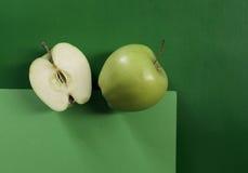 Duas maçãs verdes no fundo verde geométrico Fotografia de Stock Royalty Free