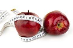 Duas maçãs vermelhas maduras e uma fita métrica Fotografia de Stock Royalty Free
