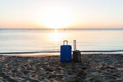 Duas malas de viagem do curso no Sandy Beach do nascer do sol com fundo do mar, conceito das férias de verão Fotos de Stock Royalty Free