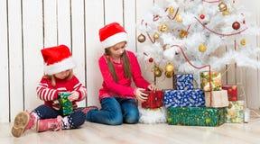 Duas meninas abrem os presentes de Natal que sentam-se no assoalho Fotografia de Stock