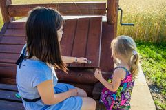 Duas meninas abriram a tampa de madeira do poço fotos de stock royalty free