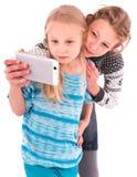 Duas meninas adolescentes fazem o selfie em um fundo branco Imagem de Stock