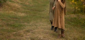 Duas meninas, adolescentes, guardando as mãos, andam na grama verde, correm na natureza fotografia de stock