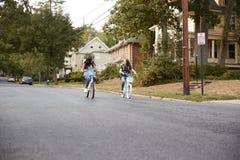 Duas meninas adolescentes que montam bicicletas na distância na rua quieta foto de stock