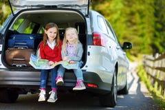Duas meninas adoráveis prontas para ir em férias com seus pais Crianças que sentam-se em um carro que examina um mapa Imagem de Stock Royalty Free