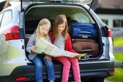 Duas meninas adoráveis prontas para ir em férias com seus pais Crianças que sentam-se em um carro que examina um mapa Fotografia de Stock Royalty Free