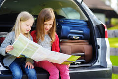 Duas meninas adoráveis prontas para ir em férias com seus pais Crianças que sentam-se em um carro que examina um mapa Fotos de Stock Royalty Free