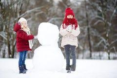 Duas meninas adoráveis que constroem um boneco de neve junto no parque bonito do inverno Irmãs bonitos que jogam em uma neve Imagem de Stock