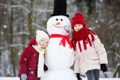 Duas meninas adoráveis que constroem um boneco de neve junto no parque bonito do inverno Irmãs bonitos que jogam em uma neve Fotos de Stock