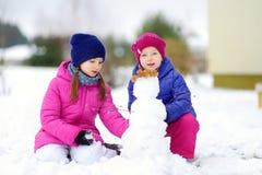 Duas meninas adoráveis que constroem um boneco de neve junto no parque bonito do inverno Irmãs bonitos que jogam em uma neve Fotografia de Stock