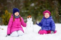 Duas meninas adoráveis que constroem um boneco de neve junto no parque bonito do inverno Irmãs bonitos que jogam em uma neve Foto de Stock