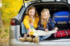 Duas meninas adoráveis que sentam-se em um tronco de carro antes de ir em férias com seus pais Duas crianças que olham para a fre Fotos de Stock