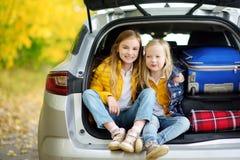 Duas meninas adoráveis que sentam-se em um tronco de carro antes de ir em férias com seus pais Duas crianças que olham para a fre Fotos de Stock Royalty Free