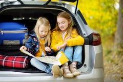 Duas meninas adoráveis que sentam-se em um tronco de carro antes de ir em férias com seus pais Duas crianças que olham para a fre Imagens de Stock
