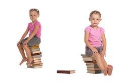 Duas meninas agradáveis que sentam-se na pilha de livros fotografia de stock royalty free