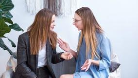 Duas meninas alegres falam um com o otro, gesticulam emocionalmente com suas mãos, discutem um assunto interessante imagens de stock