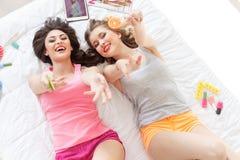 Duas meninas alegres que encontram-se no quarto Fotografia de Stock