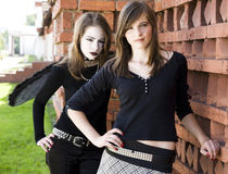 Duas meninas aproximam a parede de tijolo imagem de stock royalty free