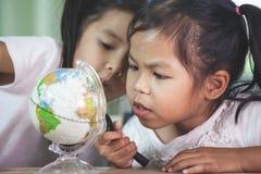Duas meninas asiáticas bonitos da criança usam a lente de aumento para olhar e estudar no globo na sala de aula fotos de stock royalty free