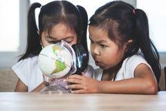 Duas meninas asiáticas bonitos da criança usam a lente de aumento para olhar e estudar no globo na sala de aula fotos de stock