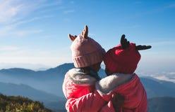 Duas meninas asiáticas da criança que vestem a camiseta e o chapéu morno que abraçam junto com o amor na névoa e na montanha boni imagens de stock royalty free