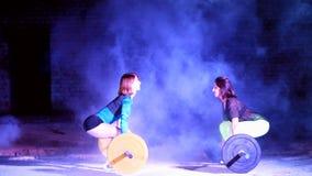 Duas meninas atléticas, atletas, fazendo exercitam com o barbell Na noite, à vista dos holofotes, um stobascope, dentro video estoque